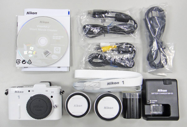 V1雙鏡組開箱後,裡面有Nikon V1相機本體、雙鏡頭、相機背帶、原廠說明書、說明光碟、ViewNX2軟體光碟、AV OUT音頻/視頻線、USB傳輸線、原廠充電鋰電池、電源線、充電器。