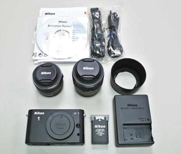 J1雙鏡組開箱後看到的是 Nikon J1相機本體、雙鏡頭、相機背帶、原廠說明書、說明光碟、ViewNX2軟體光碟、AV OUT音頻/視頻線、USB傳輸線、原廠充電鋰電池、電源線、充電器。